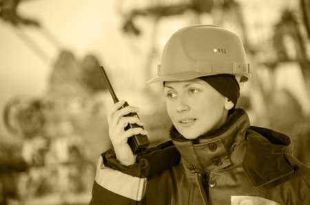 trabajador petrolero: Trabajador de sexo femenino en el campo petrolero hablando en la radio que desgasta el casco rojo y ropa de trabajo azul. Sitio industrial background.Toned sepia.