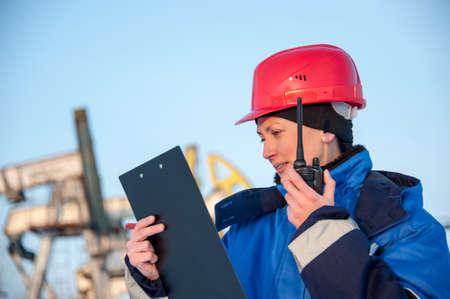 casco rojo: Trabajador de sexo femenino en el campo petrolero hablando en la radio que desgasta el casco rojo y ropa de trabajo azul. fondo de emplazamientos industriales.