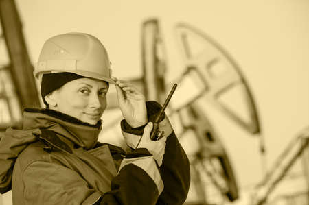 professional woman: Female worker in the oil field talking on the radio wearing red helmet and blue work clothes. Industrial site background.Toned sepia.