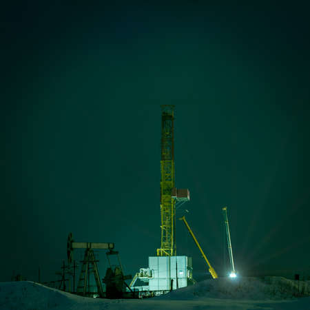 pump jack: Night view of a derrick drilling and oil pump jack. Stock Photo