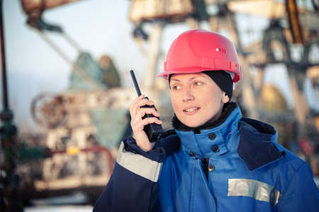 Female worker in the oil field talking on the radio wearing red helmet and blue work clothes. Industrial site background. Toned. Stock Photo