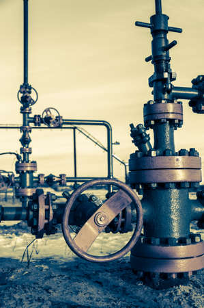 Group of wellhead. Oilfield with sand ground. Oil and gas . Toned. Stock Photo