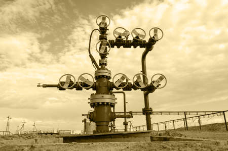 Wellheads and pipeline with valves. Oil and gas theme. Toned sepia.