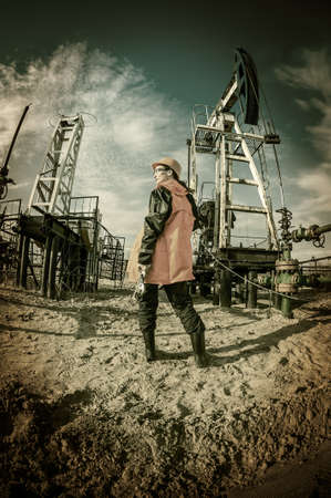 Women worker in the oil field, with wrenches in a hands, orange helmet and work clothes. Industrial site background. Toned. Stock Photo
