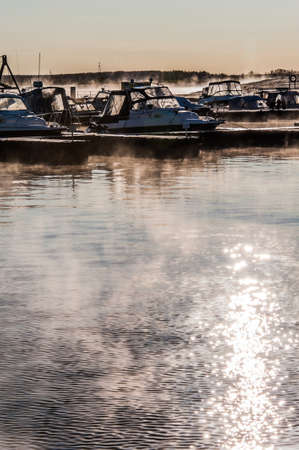 Boats and yachts moored at the port. Glittering sea surface against sunrise. Morning fog.