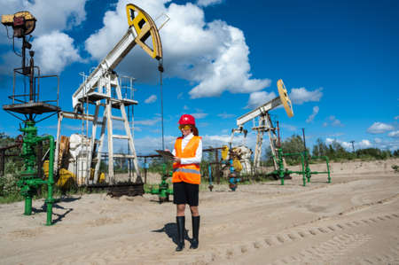 pump jack: Beautiful woman engineer in the oilfield wearing red helmet and work clothes. Pump jack and wellhead valve background. Oil and gas concept.