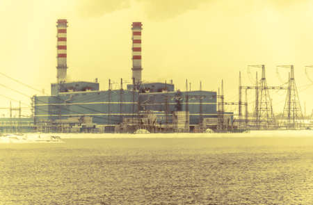 power industry: Gas power plant. Pipes with smoke. Lake with fog foreground. Energy industry concept. Toned.