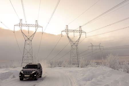 winter weather: Moving car on snowy winter road among frozen trees after sleet. Cold weather, slippery road. Transmission tower background.