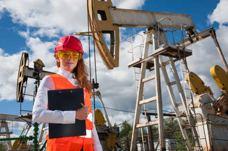 wellhead: Beautiful woman engineer in the oilfield wearing red helmet and work clothes. Pump jack and wellhead valve background. Oil and gas concept.