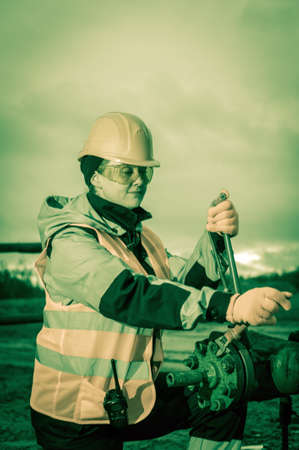 work worker: Women worker in the oil field, with wrenches in a hands, orange helmet and work clothes. Industrial site background. Toned. Stock Photo