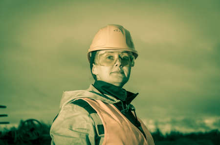 industrial industry: Closeup portrait of female industrial worker, engineer wearing helmet and protective glasses. Industry, manufacturing theme.