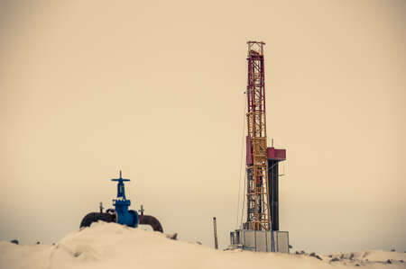 pump jack: Pump jack and oil rig in the oilfield situated in the beautiful winter forest. Environmental pollution. Oil and gas concept. Stock Photo