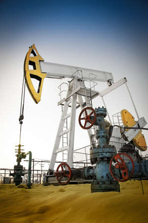 pump jack: Oil pump jack and wellhead in the oilfield. Oil and gas concept. Stock Photo