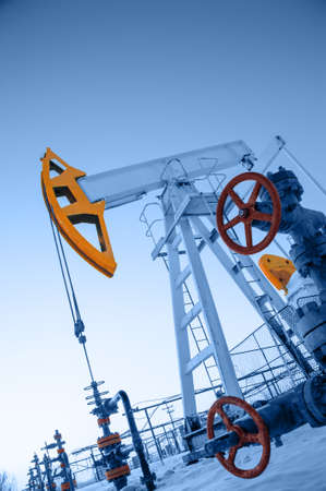 Oil pump jack and wellhead in the oilfield. Oil and gas concept. Stock Photo