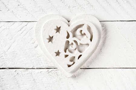 Wood heart shape on a vintage wooden background.