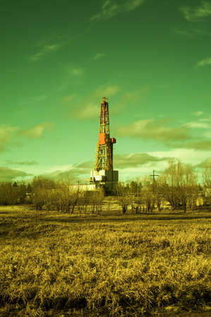 Landscape with a drilling rig at an oil field. Sunny day, early spring. Industrial landscape. Russia, Western Siberia.