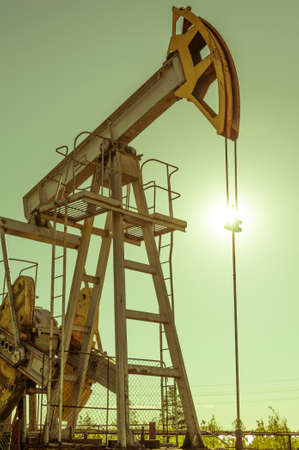 Oil pumpjack, industrial equipment. Rocking machines for power genertion. Extraction of oil. Petroleum concept. Stock Photo