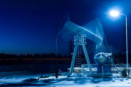Working oil pump at night time. Oilfield during winter. Oil and gas concept. Motion blur. Stock Photo