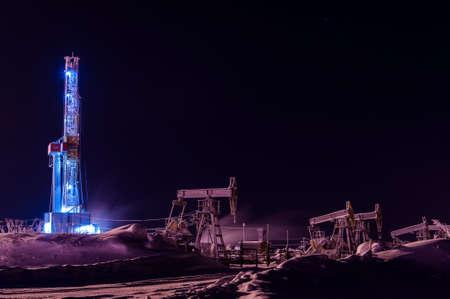 Plataforma de perforación de petróleo y gas en la noche. Operación de plataforma de perforación y gato de bomba en la plataforma petrolera.