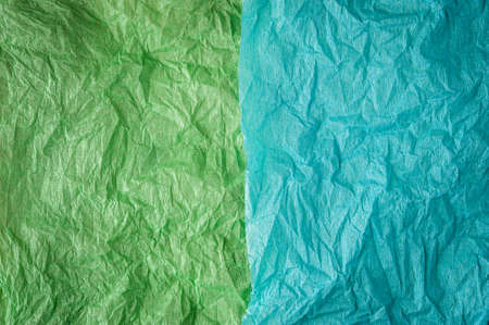 Multi-colored crumpled real vivid paper sheets texture background. Green, cyan. 免版税图像
