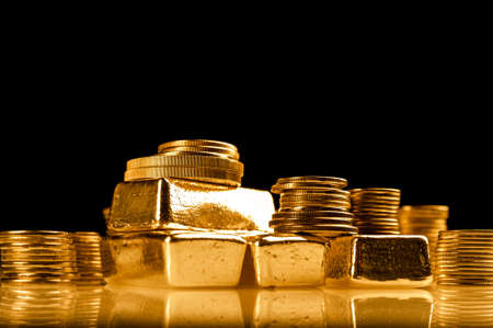 Gold bullions and stack of coins. Background for finance banking concept. Trade in precious metals.