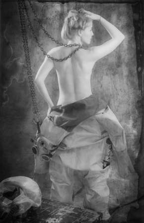 Nude young woman with blond hair and freckles with chain in a vintage diving suit. Black and white.