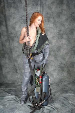Jeune femme nue aux cheveux rouges et taches de rousseur avec une chaîne dans ses mains dans un scaphandre vintage. Banque d'images