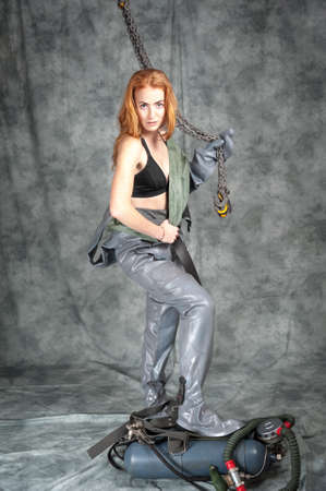 Nude young woman with red hair and freckles with a chain in her hands in a vintage diving suit.