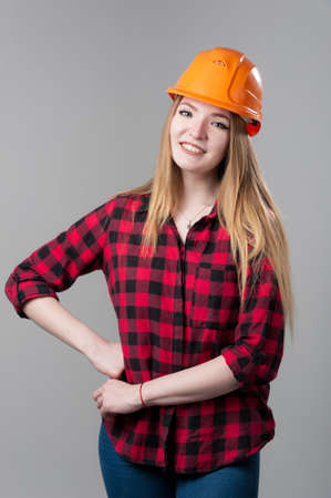 Portrait of a young attractive woman with blond hair in orange helmet on a neutral gray background.