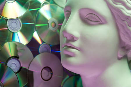 Antique statue of Venus head close up on a glitter CDs background. Concept of music, style, vintage. Фото со стока
