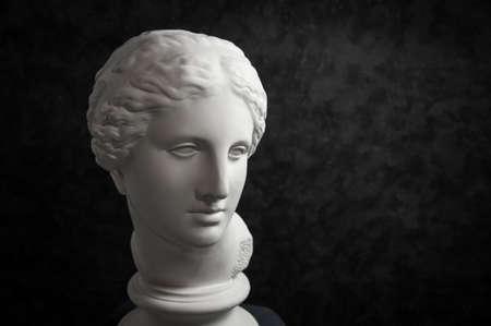 Gipskopie der antiken Statue Venuskopf auf einem dunklen strukturierten Hintergrund. Frauengesicht der Gipsskulptur.