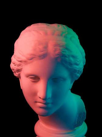 Copie de gypse de l'ancienne statue de la tête de Vénus isolée sur fond noir. Visage de femme sculpture en plâtre. Multicolore tonique.