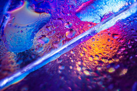 Background in the style of the 80-90s. Real texture of broken glass or ice and drops in bright acid colors.