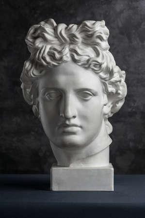 Gipskopie des antiken Apollo-Statue-Kopfes auf dunklem strukturiertem Hintergrund. Gipsskulptur Mann Gesicht.