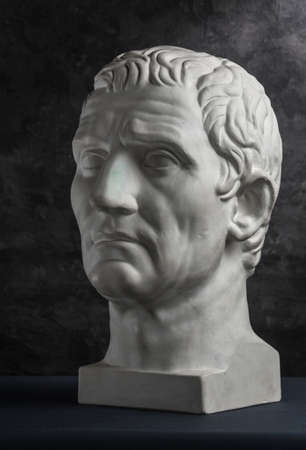 Gypsum copy of ancient statue Augustus head on dark textured background. Plaster sculpture man face. Archivio Fotografico - 128908793