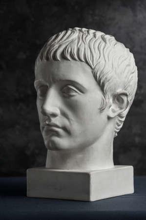 Copie de gypse de la tête de Germanicus statue antique sur fond texturé sombre. Visage d'homme de sculpture en plâtre.