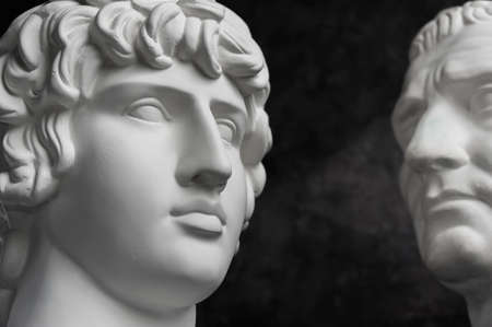 Gypsum copy of ancient statue Augustus and Antinous head on dark textured background. Plaster sculpture mans face. Banque d'images - 128908842