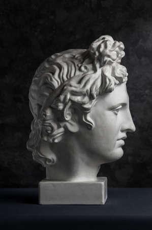 Gypsum copy of ancient statue Apollo head on dark textured background. Plaster sculpture man face. Banque d'images - 128908845