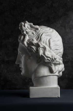 Gypsum copy of ancient statue Apollo head on dark textured background. Plaster sculpture man face. Banque d'images - 128908838