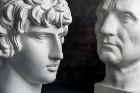 Gypsum copy of ancient statue Augustus and Antinous head on dark textured background. Plaster sculpture mans face. Banque d'images - 128908841