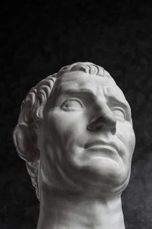 Gypsum copy of ancient statue Augustus head on dark textured background. Plaster sculpture man face. Banque d'images - 128908846