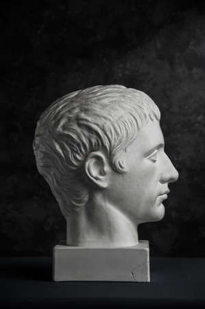 Gypsum copy of ancient statue Germanicus head on dark textured background. Plaster sculpture man face. Banque d'images - 128908848