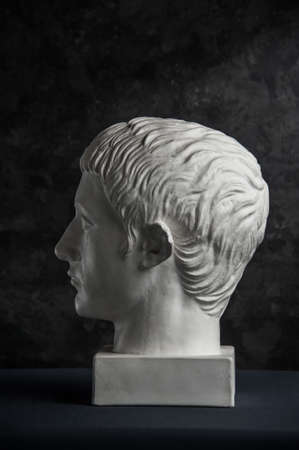 Gypsum copy of ancient statue Germanicus head on dark textured background. Plaster sculpture man face. Banque d'images - 128908852