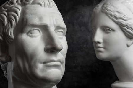 Gypsum copy of ancient statue Augustus and Venus head on dark textured background. Plaster sculpture mans face. Banque d'images - 128908856