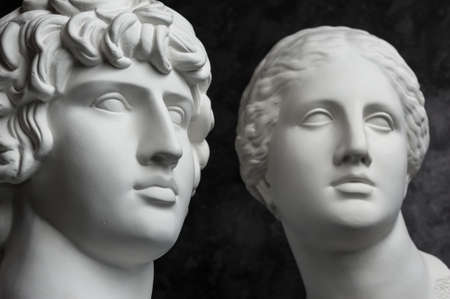 Gypsum copy of ancient statue Antinous and Venus head on dark textured background. Plaster sculpture face. Banque d'images - 128908857