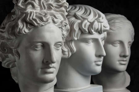 Gypsum copy of ancient statue Apollo, Antinous and Venus head on dark textured background. Plaster sculpture face. Banque d'images - 129185348