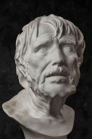 Gypsum copy of ancient statue Seneca head on dark textured background. Plaster sculpture man face. Archivio Fotografico - 132294010