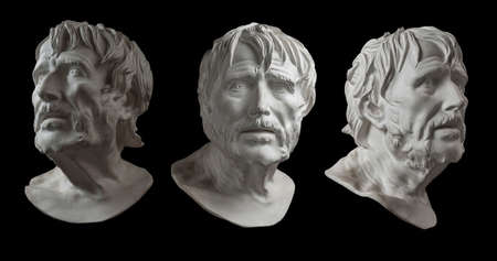 Three gypsum copy of ancient statue head of Lucius Seneca isolated on black background. Plaster sculpture aged man face. Banco de Imagens