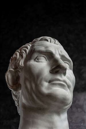 Gypsum copy of ancient statue Augustus head on dark textured background. Plaster sculpture man face. Archivio Fotografico