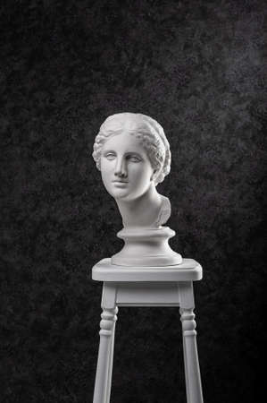 Gypsum copy of ancient white statue of bust of Venus on chair with textured black background .Plaster sculpture woman face. The goddess of love in Greek mythology. Renaissance epoch.